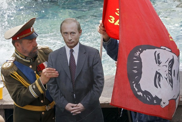 A men dressed up to resemble Russian Czar Nicholas II, left, sets up a cardboard cutout of Russian President Vladimir Putin and another man, behind the flag, holds a red flag with former Soviet leader Josef Stalin, as they wait for tourists at Manezh Square near Red Square in Moscow, Russia, Friday, July 13, 2012. (AP Photo/Misha Japaridze)