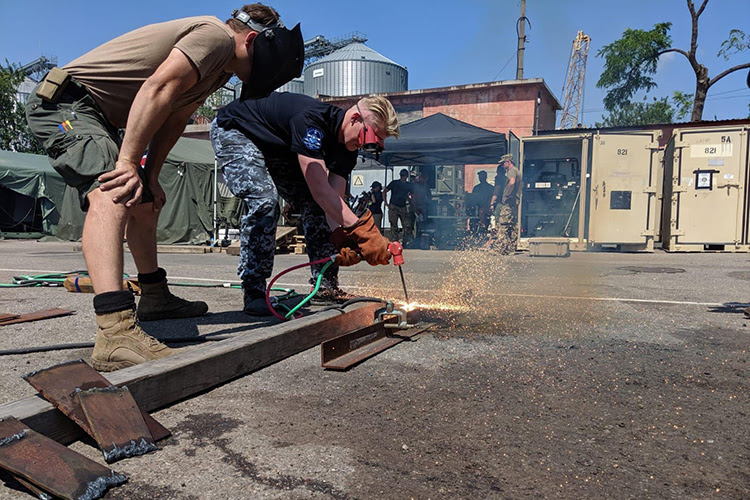 Construction Mechanic 2nd Class Jordan Glensor assists a Ukrainain sailor with an exothermic cutter during a practical training session in support of exercise Sea Breeze 2019 in Odesa, Ukraine, July 4, 2019. Sea Breeze is a U.S. and Ukraine co-hosted multinational maritime exercise held in the Black Sea and is designed to enhance interoperability of participating nations and strengthen maritime security and peace within the region. (U.S. Navy photo by Lt. Amanda Caffey)